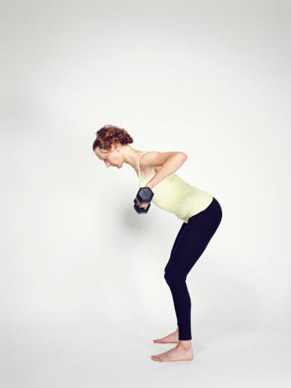 A young woman against a white background, lifting dumbells