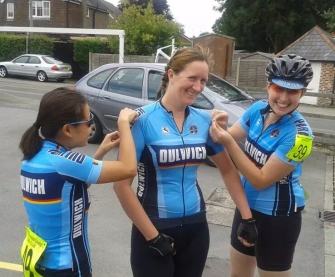 Two women in Dulwich Jerseys help another woman in a Dulwich jersey pin on her race numbers