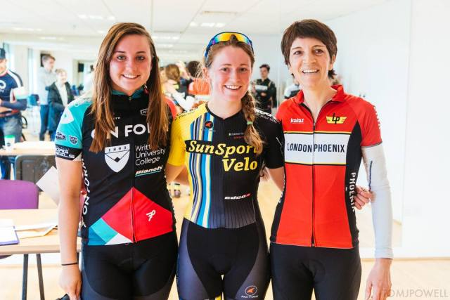 Three women, in their cycling kits, stand arm in arm as the podium